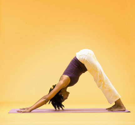 Woman in downward dog yoga stretch, side view